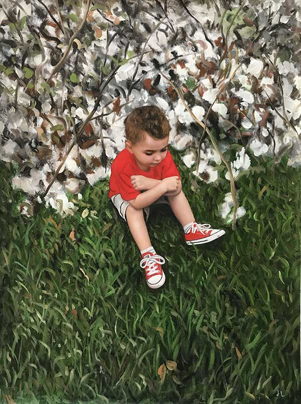 boy in a red shirt sitting in the grass against white cherry blossom tree